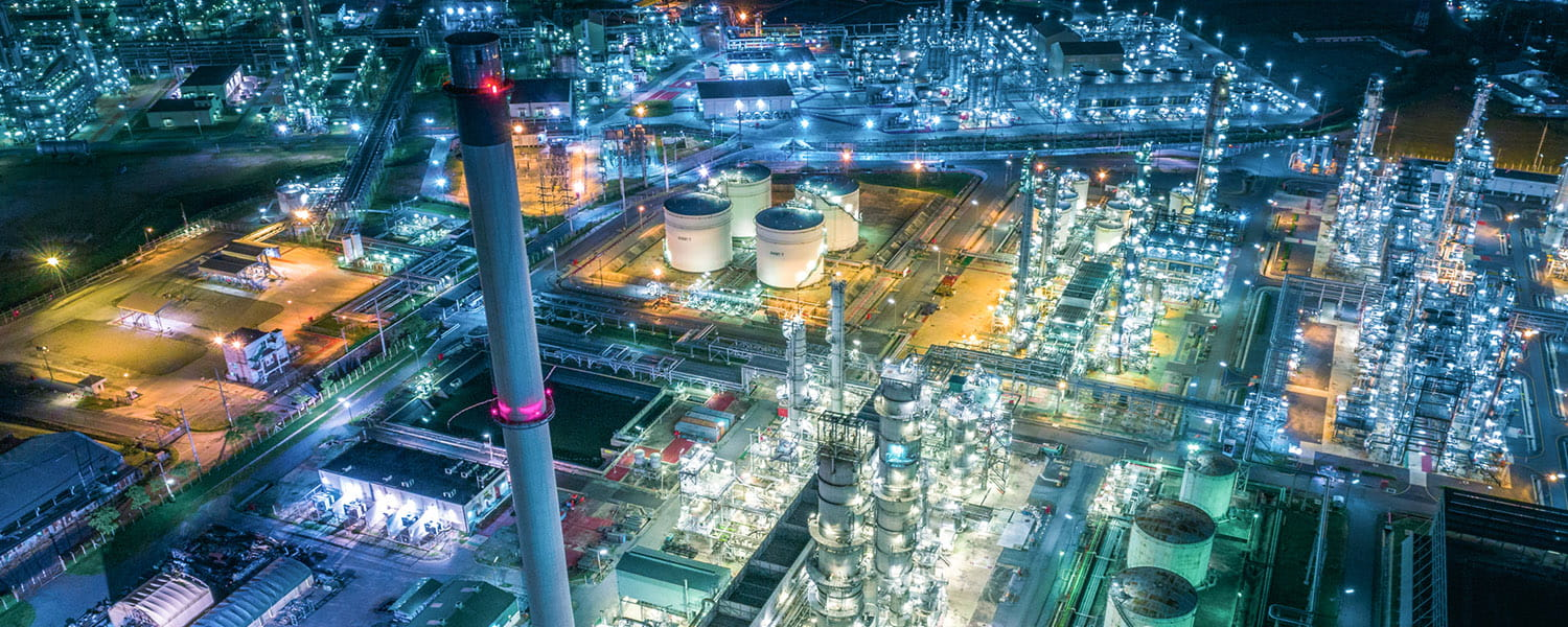 Aerial view of a petrochemical plant at night, with lots of bright lights.