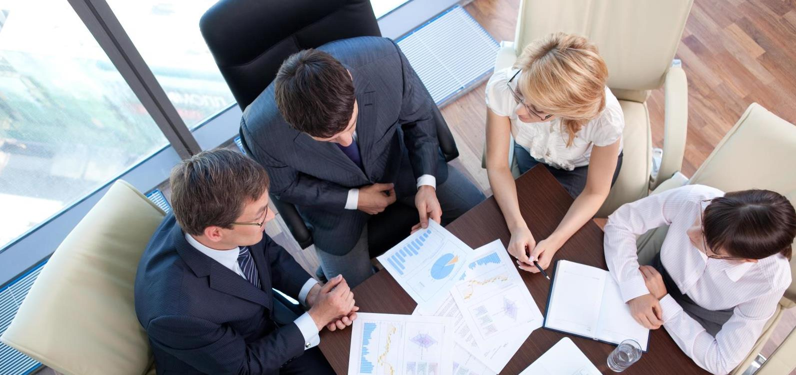 Top down view of a group of consultants at a meeting table with papers and graphs in front of them