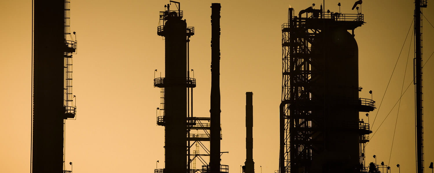Top of towers of a refinery, with an orange sky background.