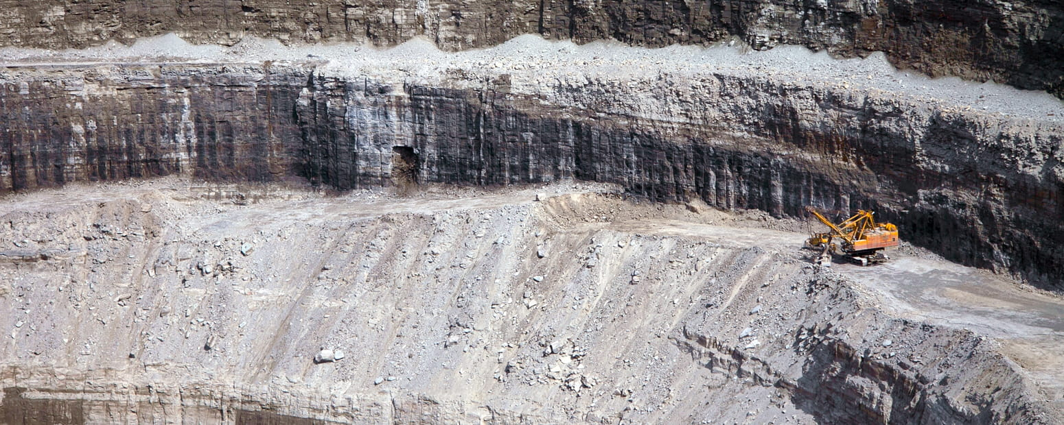 Wall of diamond mine with machinery in the foreground