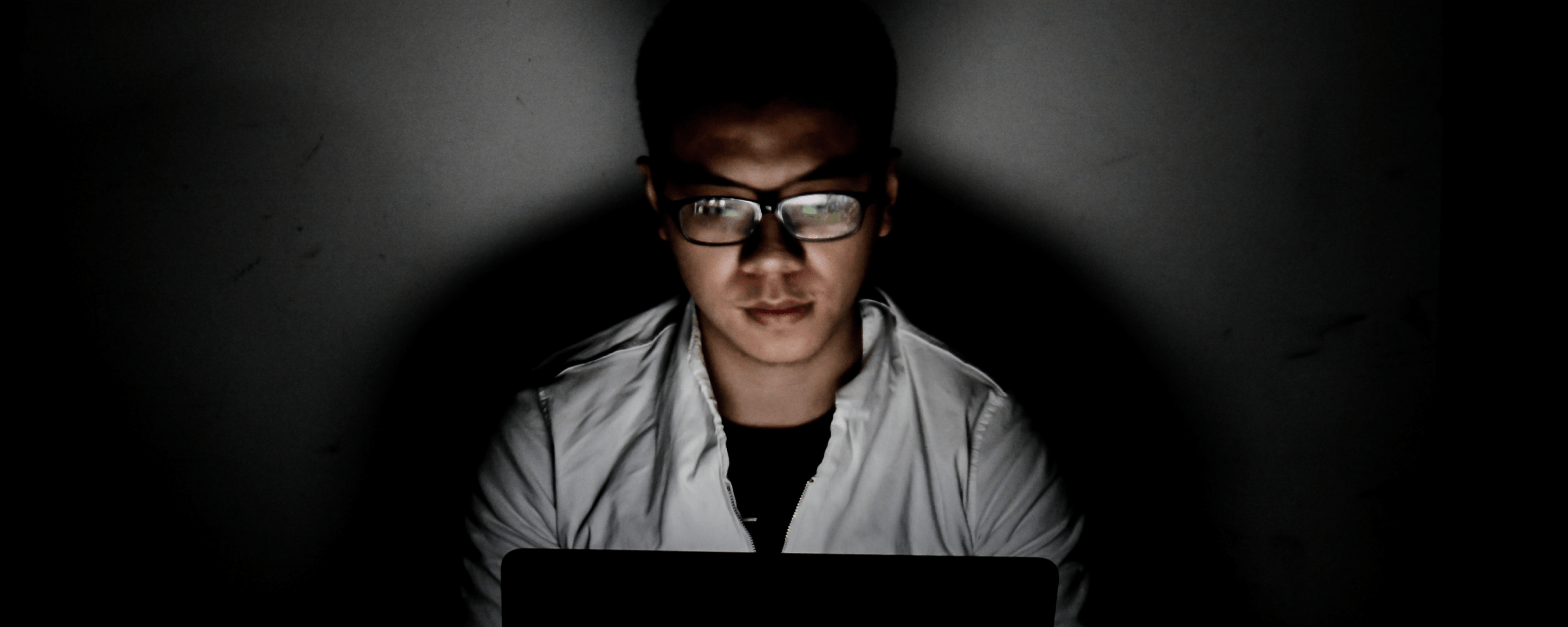 Man on computer in dark room