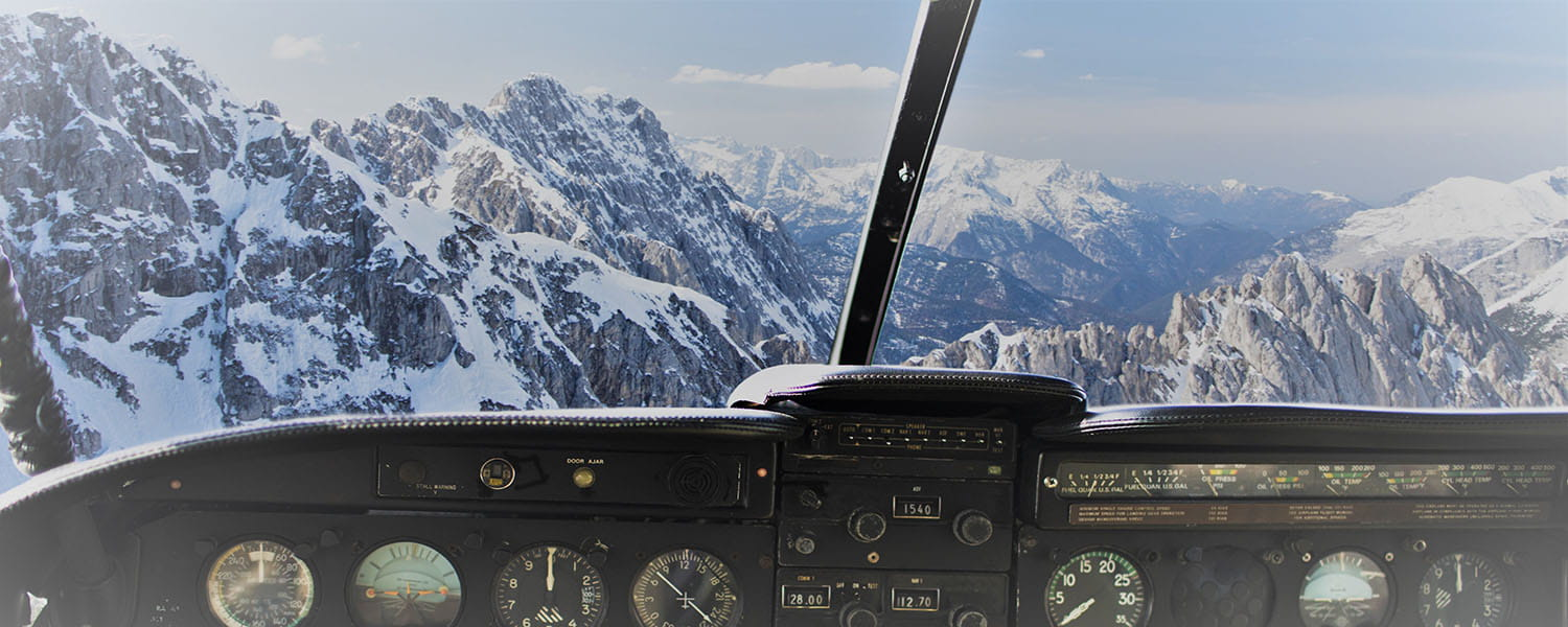 Looking out of a plane from the cockpit facing snow covered mountains