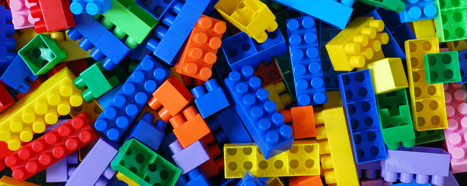 Pile of various colored children's building blocks.